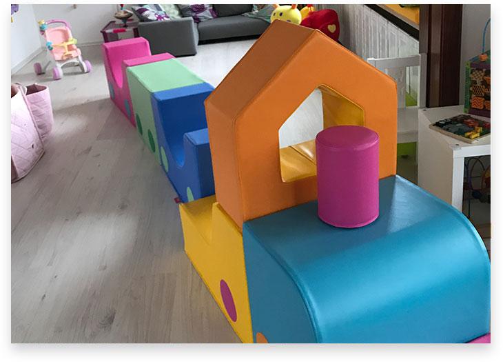 5Stars Kindertagespflege Lübeck Innenaufnahme Wohnzimmer Leseecke und Spielzeuglokomotive